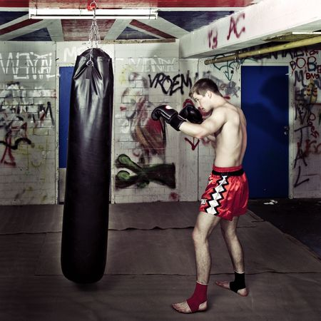 cross processed: Cross processed image of a boxer practising in a basement with a boxing bag Stock Photo