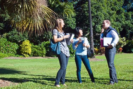 Three students in the park, on their way to college, making fun on a bright, sunny day photo