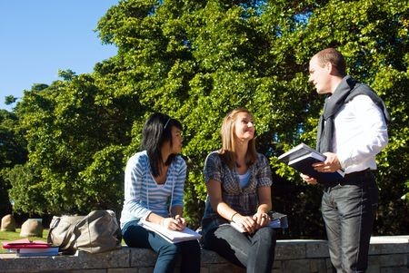 students talking: Three students talking on a small wall in a university park on a beautiful sunny day
