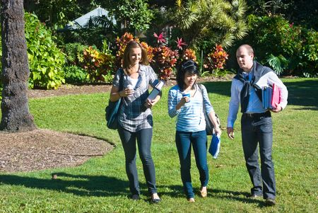 Three students walking through the botanical gardens, on their way to class Stock Photo - 6562841