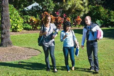 Three students walking through the botanical gardens, on their way to class Stock Photo - 6562841