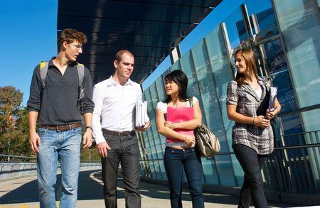 Cuatro estudiantes universitarios, caminando a clase sobre un puente moderno en un hermoso día soleado
