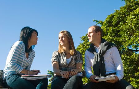 Three students talking casually in a university park on a beautiful sunny day photo