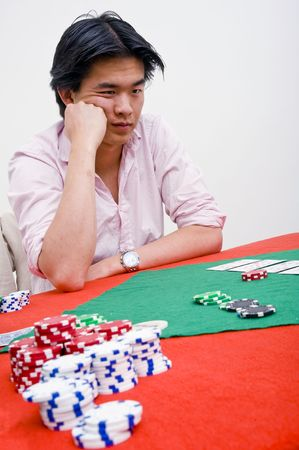 deceitful: An Asian poker player being unhappy after losing a round at poker with a bad hand of cards