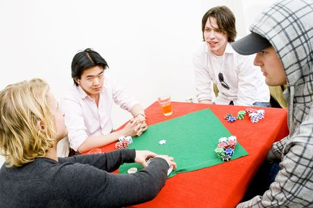 deceitful: Four people sitting around a square poker table for a private casual game Stock Photo