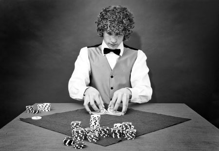 A dealer shuffling cards at a poker table photo