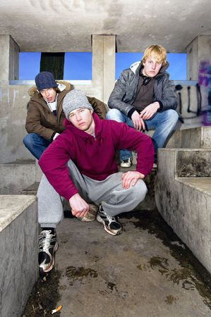 Three angry looking gangmembers in a dirty, concrete bunker at dusk. Stock Photo - 6612511