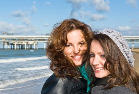 Portrait of two young women on the beach on a beautiful autumn afternoon photo