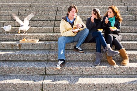 Three young adults sitting on concrete stairs, eating fish and chips, wilst two seagulls steal a bit of cod cheeks,  photo