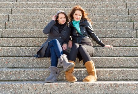 Two young woman sitting on steps on an autumn afternoon photo