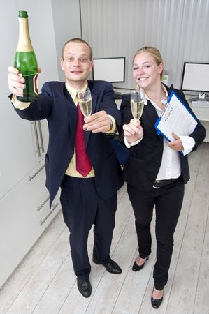 Two colleagues celebrating a business deal with a bottle of champagne, holding the file with the signed contract photo