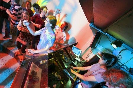 fiesta dj: Manada de fiesta en una discoteca de moda con DJs en el trabajo y la gente bailando en la pista de baile
