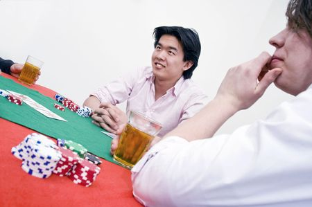 deceitful: An Asian man sittingat the poker table during a game, ambiguously smiling at the competition