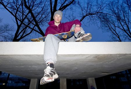 streetlife: Lifestyle portrait of an unhappy looking youth with a skateboard in his hand sitting on the concrete ledge of a bunker Stock Photo