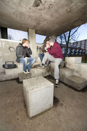 suburbian: Three adolescent youths lighing cigarettes in a shelter in a suburbian area