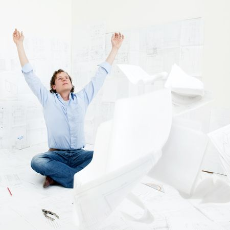revising: An overworked engineer throwing the technical drawings hes been revising towards the camera, raising his hands and head in the air in dispair