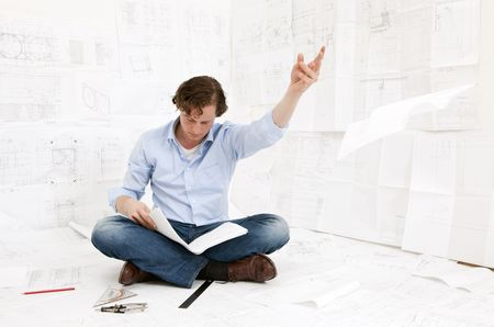 Young mechanical engineer, sitting on the floor, surrounded by complexe technical drawings of an injection mould, throwing away a drawing, whilst remaining focused on the documents in his hand photo