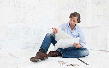 Young mechanical engineer, surrounded by huge technical drawings, sitting on the floor on more designs, going over the technical details, with a red pencil in his hand photo