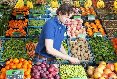 grocer: A greengrocer at work amidst various crates of fresh fruit and vegetables in a shop Stock Photo