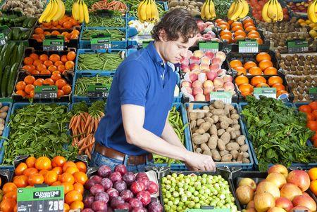 naranjas: Un frutero en el trabajo en medio de varias cajas de fruta fresca y verduras en una tienda Foto de archivo
