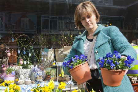 violets: Woman comparing two pots with violets in front of a florist