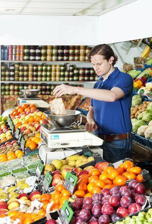 greengrocer: Frutero con un peso de alimentos frescos en una escala digital