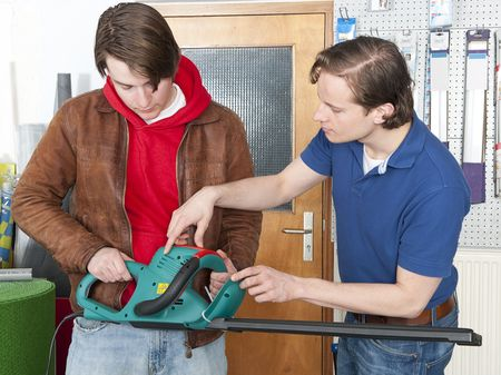 demonstrating: Salesman at a hardware store demonstrating and selling hedgeshears to a customer Stock Photo