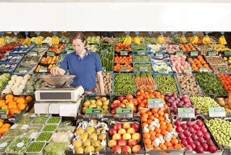 greengrocer: Un tendero verde con un peso de verduras en una tienda de comestibles