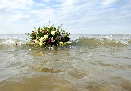Bouquet afloat in the gentil surf of the north sea, as metaphore of rememberance of a watery grave photo