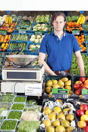 A greengrocer standing behind the display counter surrounded by fresh fruit and vegetables photo