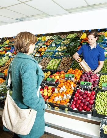 greengrocer: Verde tendero servir a un cliente detr�s del mostrador de visualizaci�n en su tienda, poner las manzanas en una bolsa de papel Foto de archivo