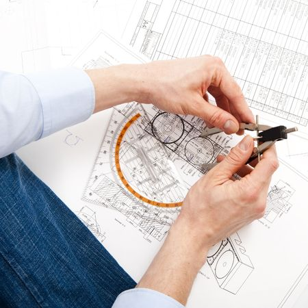 revising: An engineer checking a technical drawing with a pair of compasses and a triangle Stock Photo