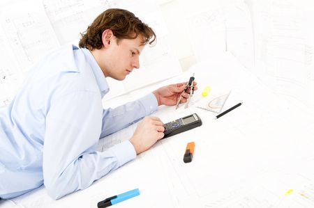 Industrial design engineer calculating measurements and tolerances on a technical drawing using a calculator photo