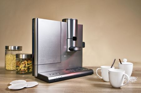 Still life with a domestic pad coffee machine on a wooden surface, country styled photo