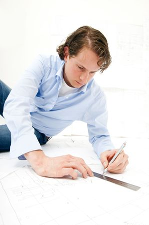 Engineer drawing a line on a set of technical drawings using a pencil and a ruler photo