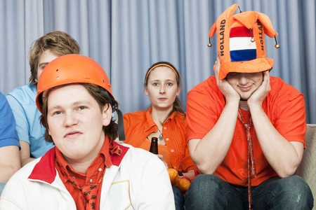 disbelief: Four soccer fans, watching a game at home, in disbelief about the outcome of the game