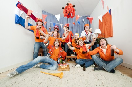 cheering fans: Group of ten cheering sports fans watching their national sports team at home