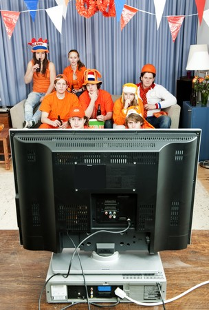 Eight tense sports fans watching a game at home on television photo