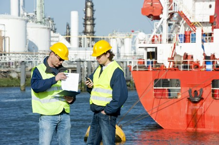 autobotte: Two harbor workers going over docking plans in at a petrochemical port Archivio Fotografico