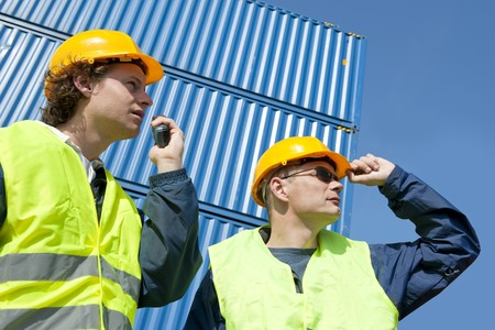 instructing: Two dock workers in safety clothing supervising and giving instructions using a walkie-talkie.