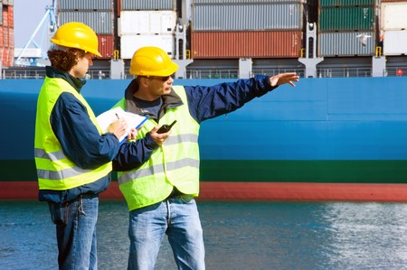 Two Dockers at work in an industrial harbor, giving instructions, and writing them down. photo