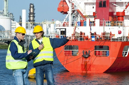 hard hats: Two dockers at work, wearing safety vests hand hard hats, in frond of a red fire boat at a petrochemical harbor