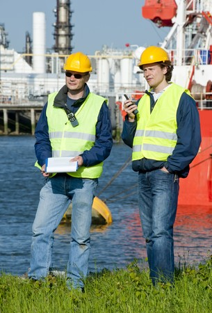 Two harbor engineers with radios, personal safety equipment and a clip board photo