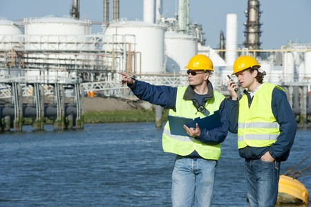 Two petrochemical engineers discussing a project outdoors