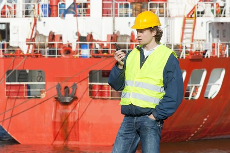 work boat: Docker on the radio with instructions in front of a huge oil tanker in an industrial harbor