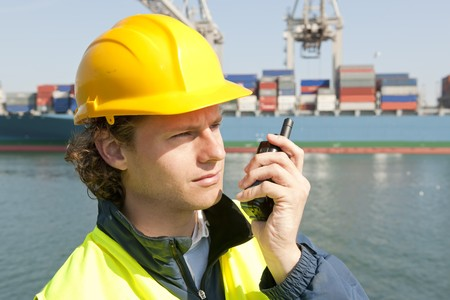 Harbor worker, listening to his radio for instructions photo