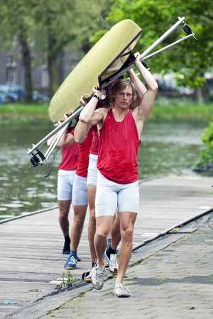 A rowing team carrying their boat to the boat house after a race Stock Photo - 7066198