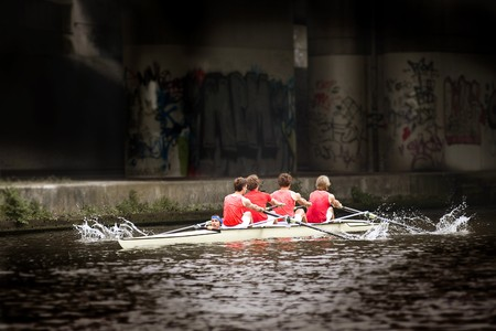 processing speed: Top sport rowing team (coxed four) emerging from the darks of a dunnel, at a high pace, splaches of water coming from the oars.