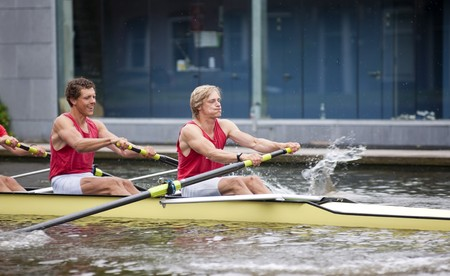 collegiate: Oarsmen during the explosive first strokes of a rowing race