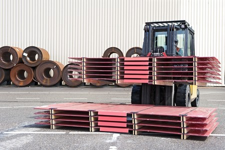 handling: Forklift stacking packaged sheets of steel
